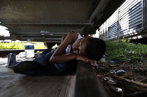 A Honduran child rests under the train, in Arriaga, Chiapas, waiting to board The Beast. Photo: Alfredo Domínguez