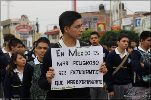 The sign the student  is holding reads: In Mexico it's more dangerous to be a student than a drug trafficker.