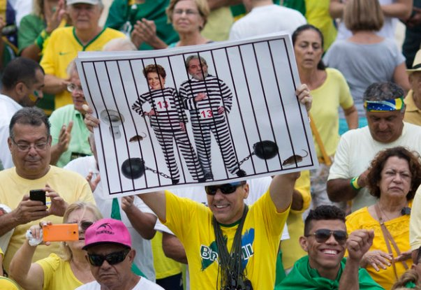 "In this March 13, 2016 file photo, a demonstrator holds a poster with the photo of Brazilian president Dilma Rousseff and former President Luiz Inacio Lula da Silva in prison stripes during a protest on Copacabana beach in Rio de Janeiro, Brazil. It was the best of times in 2009 when Rio was awarded the games, championed by then-President Luiz Inacio Lula da Silva. He called it a ""sacred day"" and praised the ""strength of Brazil's economy,"" which shrank by 4 percent in 2015 with no improvement in sight. (AP Photo/Silvia Izquierdo, File)"