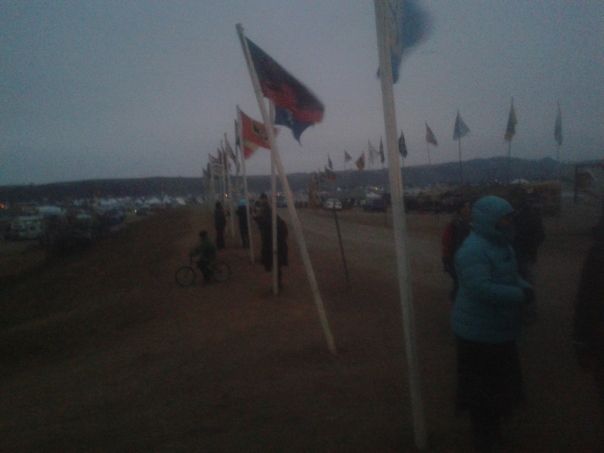 Water protectors are bundled up as the wind blows on Flag Road in the Oceti Sakowin Camp, North Dakota. Flags are billowing, with tents and hills in the background.